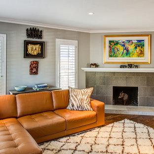 Ejemplo de salón cerrado, bohemio, pequeño, con paredes grises, suelo de madera en tonos medios, chimenea de esquina, marco de chimenea de baldosas y/o azulejos y televisor independiente