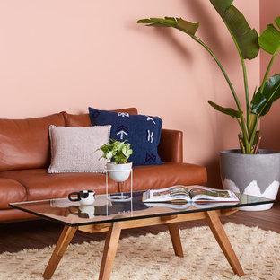 Modelo de salón abierto, contemporáneo, pequeño, con paredes rosas, suelo vinílico y suelo marrón
