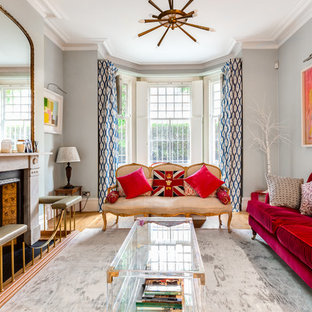 Inspiration for a medium sized eclectic formal living room in London with grey walls, a standard fireplace and medium hardwood flooring.