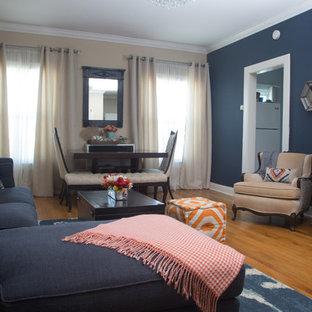 Modelo de salón cerrado, ecléctico, pequeño, sin chimenea, con paredes azules, suelo de madera clara y televisor retractable