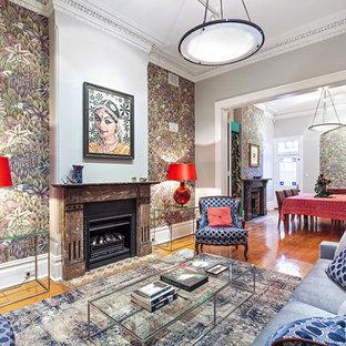 Immagine di un soggiorno eclettico di medie dimensioni e chiuso con pavimento in legno massello medio, camino classico, pavimento marrone, sala formale e pareti grigie