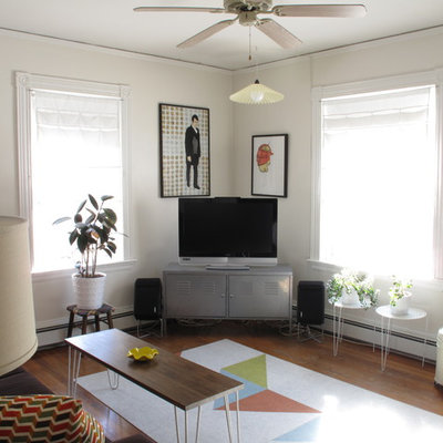 Living room - eclectic medium tone wood floor living room idea in Boston with white walls and a tv stand