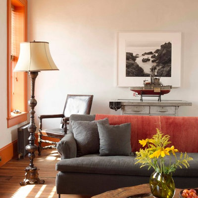 Eclectic medium tone wood floor living room photo in New York with white walls