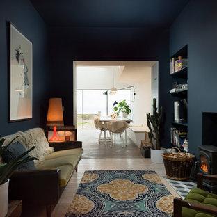 Ispirazione per un soggiorno bohémian di medie dimensioni e aperto con pareti blu, parquet chiaro, stufa a legna e cornice del camino in intonaco