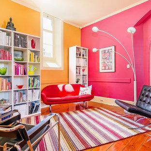 Ejemplo de biblioteca en casa abierta, bohemia, grande, con paredes multicolor y suelo de madera clara