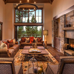 Living room - rustic dark wood floor living room idea in Sacramento with beige walls, a standard fireplace and a stone fireplace