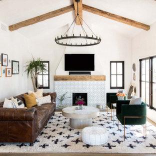 ロサンゼルスの中くらいの地中海スタイルのおしゃれなLDK (白い壁、無垢フローリング、標準型暖炉、タイルの暖炉まわり、壁掛け型テレビ、茶色い床、表し梁、三角天井) の写真