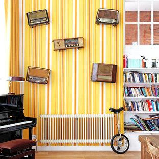 Esempio di un grande soggiorno eclettico stile loft con pareti gialle
