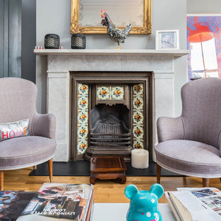 Photo of an eclectic living room in London with grey walls, medium hardwood flooring, a standard fireplace, a tiled fireplace surround and brown floors.