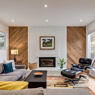 Großes, Repräsentatives, Fernseherloses, Abgetrenntes Retro Wohnzimmer mit weißer Wandfarbe, braunem Holzboden, Kamin, Kaminsims aus Backstein und beigem Boden in Calgary
