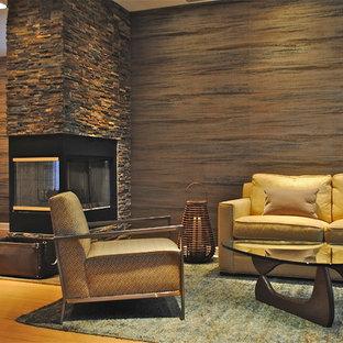 アトランタの中サイズのおしゃれなLDK (フォーマル、マルチカラーの壁、淡色無垢フローリング、両方向型暖炉、石材の暖炉まわり) の写真