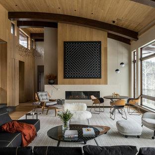 Inspiration för ett stort funkis allrum med öppen planlösning, med mellanmörkt trägolv, en bred öppen spis, en spiselkrans i sten, ett finrum, beige väggar och brunt golv
