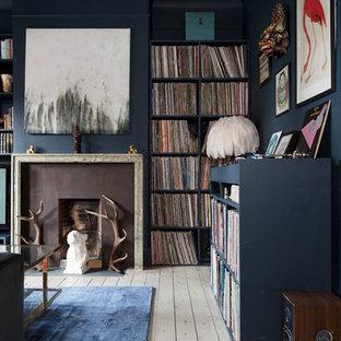 Imagen de salón ecléctico, de tamaño medio, con paredes azules, suelo de madera pintada, chimenea tradicional y marco de chimenea de piedra