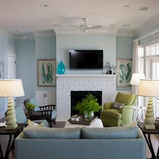 Imagen de salón abierto, costero, de tamaño medio, con paredes azules, suelo de madera oscura, chimenea tradicional, marco de chimenea de ladrillo y televisor colgado en la pared