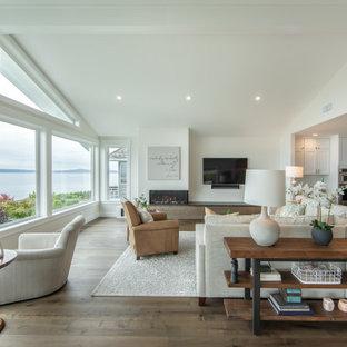 Immagine di un grande soggiorno classico aperto con pareti bianche, parquet scuro, camino ad angolo, cornice del camino in metallo, TV a parete e pavimento marrone