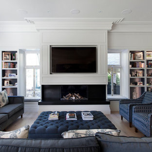 Classic living room in Cheshire with white walls, medium hardwood flooring, a standard fireplace, a wall mounted tv and brown floors.