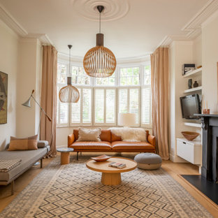 This is an example of a scandinavian living room in London with beige walls, light hardwood flooring, a standard fireplace and beige floors.