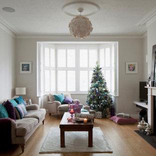 Foto de salón abierto, clásico renovado, grande, con suelo de madera clara, chimenea tradicional, marco de chimenea de piedra, televisor en una esquina y suelo marrón