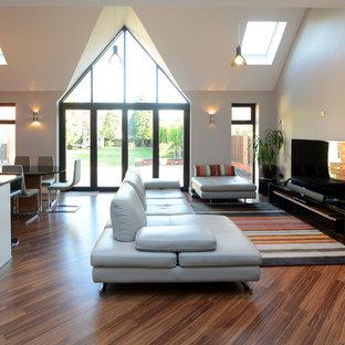 Modelo de salón abierto, contemporáneo, con parades naranjas y televisor independiente