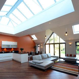 Esempio di un ampio soggiorno minimal aperto con pareti arancioni