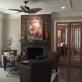 Repräsentatives, Offenes Klassisches Wohnzimmer mit beiger Wandfarbe, dunklem Holzboden, Kaminumrandung aus gestapelten Steinen und braunem Boden in Charleston