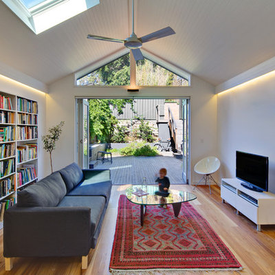 Living room - mid-sized contemporary open concept light wood floor living room idea in Sydney with white walls and a tv stand