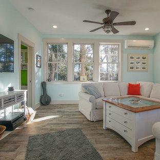 チャールストンの広いビーチスタイルのおしゃれなLDK (青い壁、無垢フローリング、暖炉なし、壁掛け型テレビ) の写真