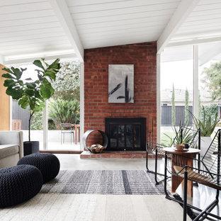Immagine di un soggiorno minimalista aperto con pareti marroni, pavimento in cemento, camino classico, cornice del camino in mattoni, pavimento grigio, soffitto in perlinato, soffitto a volta e pareti in legno