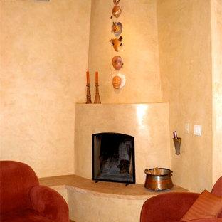 Foto di un soggiorno stile americano chiuso con pareti beige, pavimento in terracotta, camino ad angolo e cornice del camino in pietra