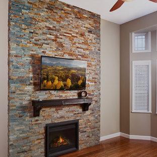 バンクーバーの中くらいのトランジショナルスタイルのおしゃれな独立型リビング (フォーマル、緑の壁、竹フローリング、標準型暖炉、石材の暖炉まわり、壁掛け型テレビ、茶色い床) の写真