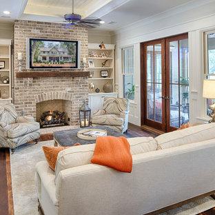 Idéer för att renovera ett mellanstort lantligt allrum med öppen planlösning, med vita väggar, mörkt trägolv, en standard öppen spis, en spiselkrans i tegelsten och en väggmonterad TV