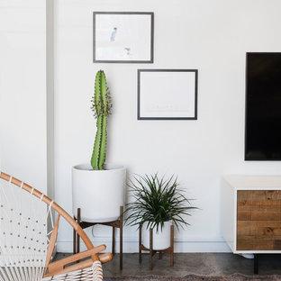 他の地域の中サイズのビーチスタイルのおしゃれなリビングロフト (白い壁、コンクリートの床、暖炉なし、壁掛け型テレビ、グレーの床) の写真