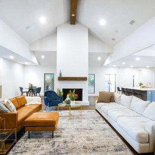 ダラスの広いミッドセンチュリースタイルのおしゃれなリビング (白い壁、濃色無垢フローリング、標準型暖炉、レンガの暖炉まわり、埋込式メディアウォール、茶色い床、三角天井、レンガ壁) の写真