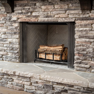 Inspiration for a craftsman open concept medium tone wood floor, exposed beam and shiplap wall living room remodel in Charlotte with beige walls and a stacked stone fireplace