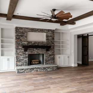 Example of an arts and crafts open concept medium tone wood floor, exposed beam and shiplap wall living room design in Charlotte with beige walls, a wood stove and a stacked stone fireplace
