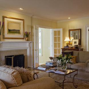 Стильный дизайн: гостиная комната в стиле фьюжн с желтыми стенами, стандартным камином и фасадом камина из камня - последний тренд