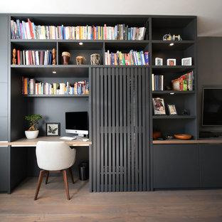 Esempio di un piccolo soggiorno minimalista con pareti grigie, parquet chiaro, nessun camino e TV a parete