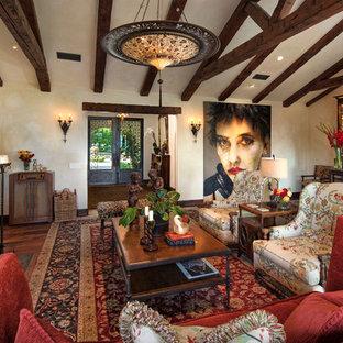 サンタバーバラの大きい地中海スタイルのおしゃれなリビング (ベージュの壁、濃色無垢フローリング、標準型暖炉、漆喰の暖炉まわり、テレビなし) の写真