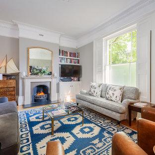 Imagen de salón para visitas abierto, clásico renovado, grande, con paredes grises, suelo de madera en tonos medios, chimenea tradicional, marco de chimenea de metal, televisor colgado en la pared y suelo amarillo