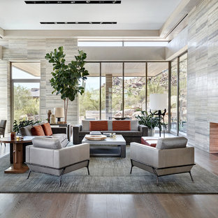 Inspiration for a huge modern formal and open concept medium tone wood floor living room remodel in Phoenix with gray walls, a standard fireplace and a stone fireplace