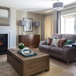 Foto på ett mellanstort vintage separat vardagsrum, med ett finrum, beige väggar, ljust trägolv, en standard öppen spis, en spiselkrans i sten och brunt golv
