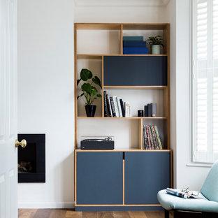 Foto de salón con rincón musical abierto, minimalista, grande, con paredes blancas, suelo de madera en tonos medios, estufa de leña, marco de chimenea de piedra, televisor retractable y suelo multicolor
