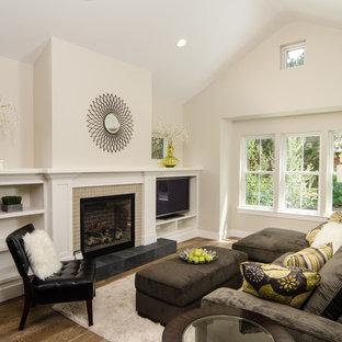 Foto di un soggiorno minimal con pareti beige, camino classico, cornice del camino piastrellata e TV autoportante