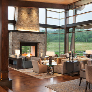 Inspiration for a rustic medium tone wood floor and brown floor living room remodel in Denver with a two-sided fireplace and a stone fireplace