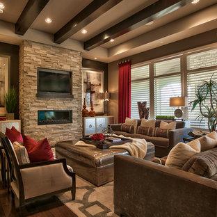 Foto de salón para visitas abierto, clásico renovado, con paredes marrones, suelo de madera oscura, chimenea lineal, marco de chimenea de piedra, televisor colgado en la pared y suelo marrón
