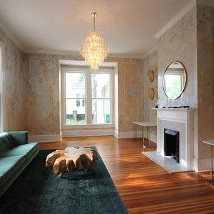 Foto de salón para visitas cerrado, clásico renovado, grande, sin televisor, con parades naranjas, suelo de madera en tonos medios, chimenea tradicional, marco de chimenea de yeso y suelo marrón