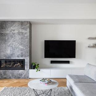 Ispirazione per un soggiorno contemporaneo di medie dimensioni e chiuso con pareti bianche, parquet chiaro, camino ad angolo, cornice del camino in pietra, TV a parete e pavimento verde