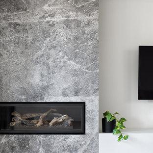 Exempel på ett mellanstort modernt separat vardagsrum, med vita väggar, ljust trägolv, en öppen hörnspis, en spiselkrans i sten, en väggmonterad TV och grönt golv