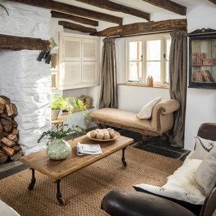 Esempio di un soggiorno country con pareti bianche, pavimento in ardesia, stufa a legna, cornice del camino in pietra e TV nascosta