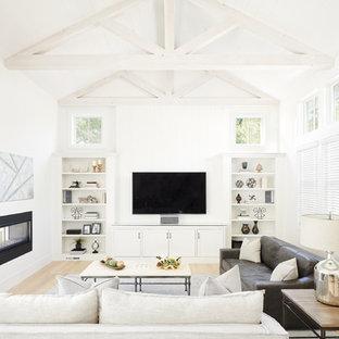 Immagine di un soggiorno country aperto con pareti bianche, parquet chiaro, camino bifacciale, TV a parete e pavimento beige